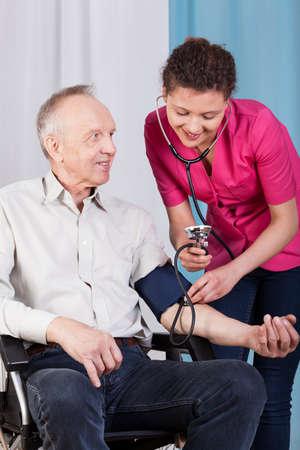 blood pressure monitor: Nurse measuring blood pressure of disabled man