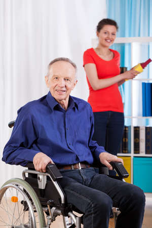 helpful: Disabled man using wheelchair and helpful granddaughter