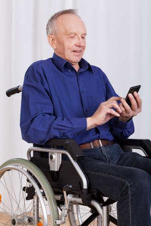 paraplegico: Hombre adulto en mensaje de texto lijado silla de ruedas Foto de archivo