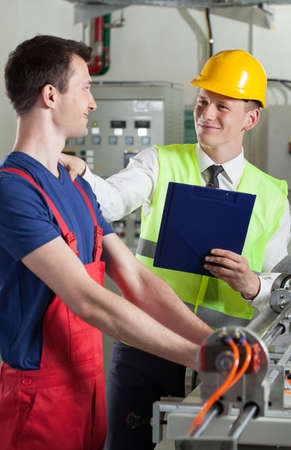 Male controller talking with factory worker, vertical
