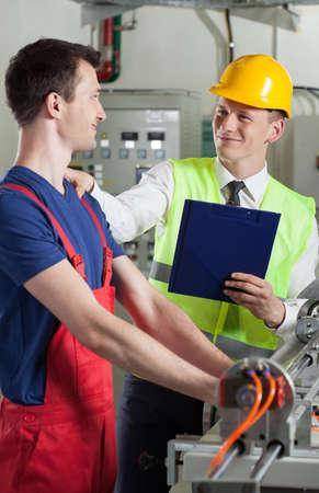 Mannelijke controller te praten met fabrieksarbeider, verticaal Stockfoto - 30793491