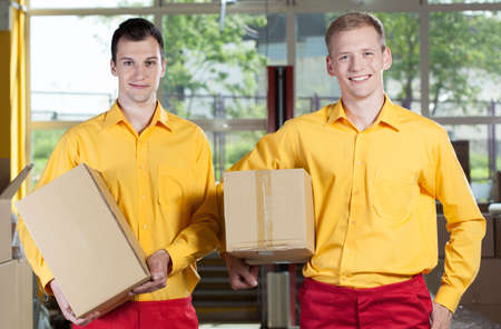 storekeeper: Smiling young storekeepers holding boxes in warehouse