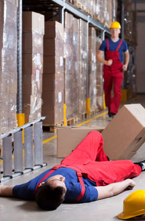 accident at work: Vertical view of a warehouseman after accident at height