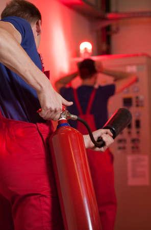 消火器を使用して工場では、垂直方向の男 写真素材