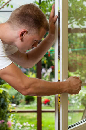Young handsome handyman working at home, vertical photo