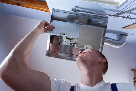 man in air: Horizontal view of a handyman fixing kitchen wall hood Stock Photo