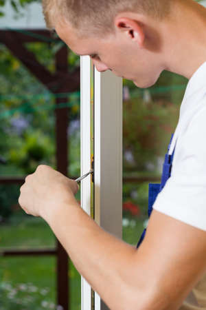 Man repairing window frame using screwdriver, vertical
