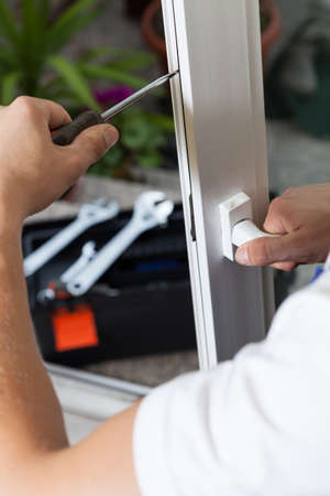 window repair: Close-up of a handyman fixing window frame
