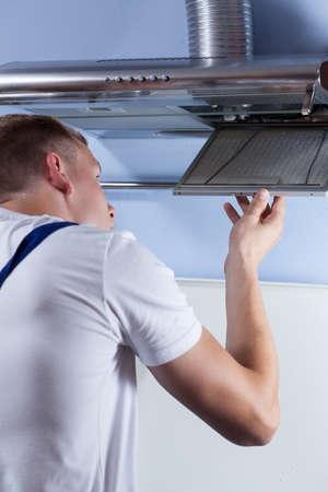 Vertical view of a man repairing kitchen hood photo