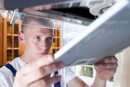Young handyman during work at kitchen, horizontal photo