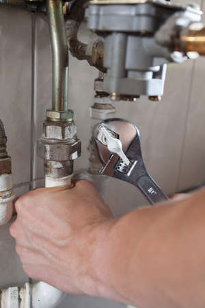 Close-up of a plumbers hands using wrench at work Stock Photo