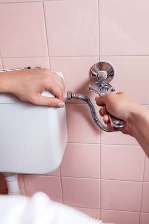 Close-up of a hands repairing toilet, vertical photo