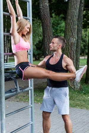 helps: Man helps woman with training in a park Stock Photo