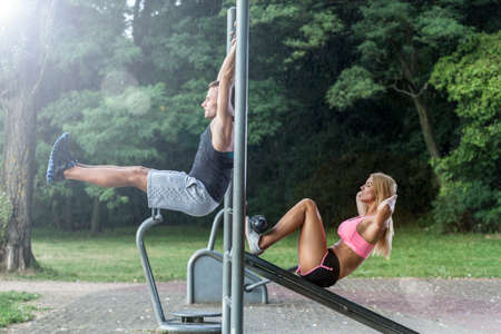 outdoor activities: Couple working out on outdoor gym, horizontal