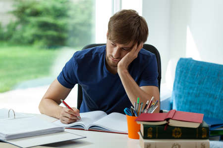 Sleepy student has to learn for exam Stock Photo