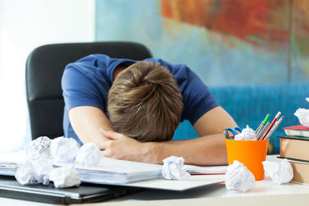 Student sleeping on the table before exam photo