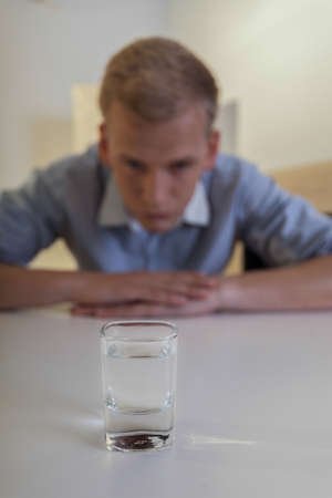Young man struggles with alcohol addiction, vertical Stock Photo