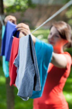 vertical garden: Woman hanging clothes on laundry line in garden, vertical Stock Photo