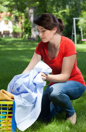 Vertical view of a young housekeeper with laundry outdoors