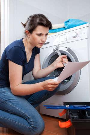 Mujer leyendo manual de instrucciones y tratar de reparar la lavadora Foto de archivo