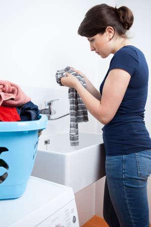 clothes washer: Vista vertical de una joven ama de casa lavando la ropa Foto de archivo