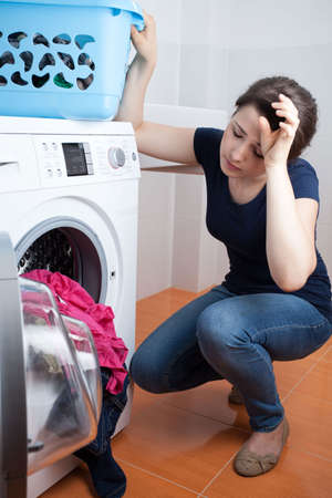 domestic chore: Tired young woman during doing housework, vertical