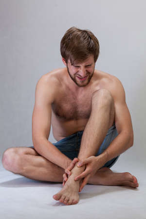 throe: Man with strong ankle pain on isolated background