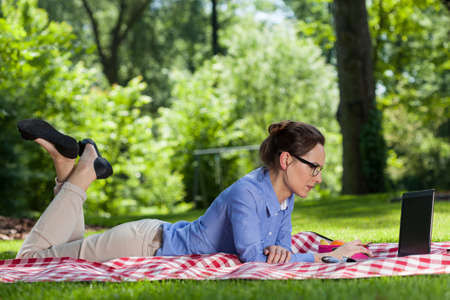 teleworking: Woman working on computer on blanket in garden Stock Photo