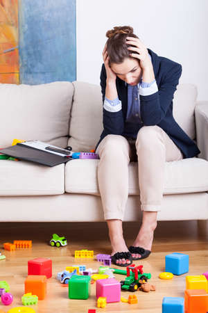 Tired working mother at home among toys Foto de archivo