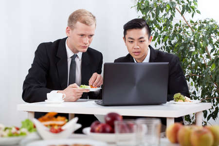 Diverse businessmen working and eating lunch, horizontal photo