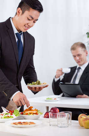 Business co-workers eating lunch during meeting photo