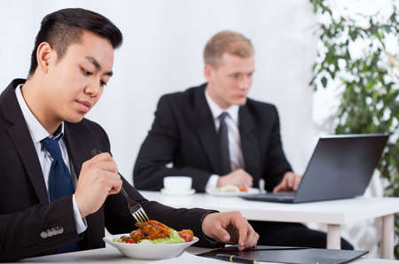 business dinner: Diverse businessmen eating healthy meal in office