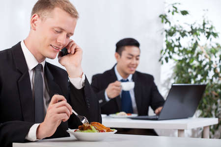 Busy diverse businessmen eating lunch in office photo