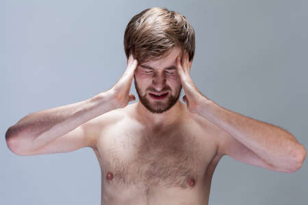 Young man with strong headache on isolated background photo