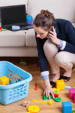 Businesswoman talking on phone and picking up toys
