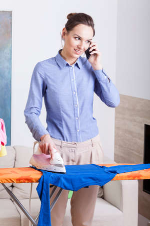 telework: Busy mother talks on phone while ironing