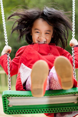 Asian girl on a swing in park photo