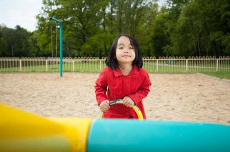 Adorable asian girl on a playground, horizontal photo