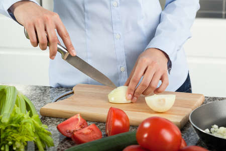 Woman cutting onion to prepare tasty dinner