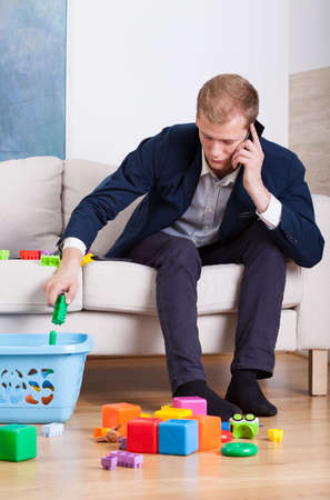 busy person: Busy young dad cleans toys at home Stock Photo