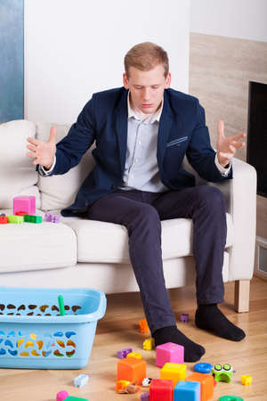 messy house: Stressed businessman gets upset at the mess in the house Stock Photo