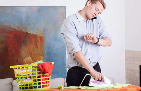 Man irons clothes and looks at his watch at home photo