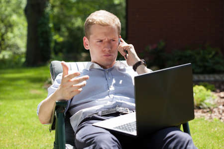 open air: Young man using a laptop and talking on the phone in the garden Stock Photo