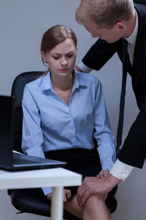 harassment: Problem of sexual harassment at work, vertical Stock Photo