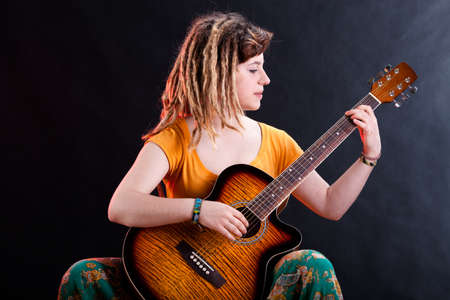 rastas: Chica joven con rastas tocando la guitarra ac�stica