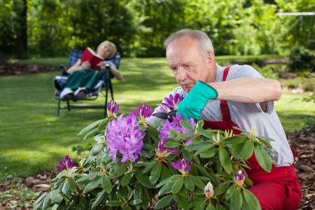 Working gardener and his resting woman, horizontal photo