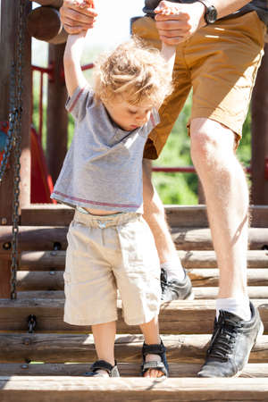 helps: Dad helps child on a playground, vertical