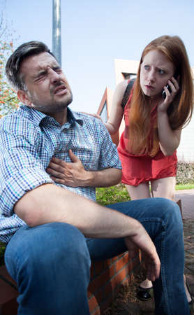 Girl calling for help for man with heart attack photo