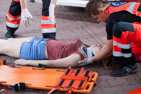 unconscious: Emergency service taking woman after accident, horizontal Stock Photo