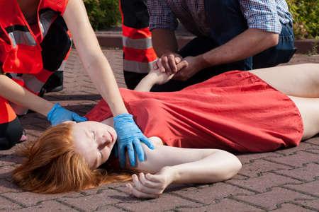 Horizontal view of paramedic helping unconscious woman photo